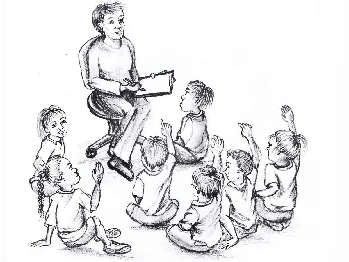 A teacher holds a clipboard a looks out at children sitting on the floor in front of her, some with hands raised.